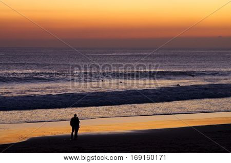 Couple At Beach By Dusk Watching Surfers