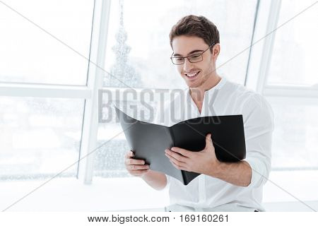 Picture of handsome young man wearing eyeglasses and dressed in white shirt holding folder over big white window background. Looking at folder.