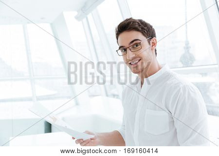 Image of cheerful man dressed in white shirt holding documents near big white window. Look at camera.
