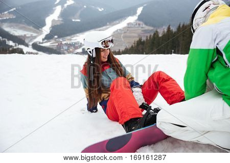 Photo of cheerful loving couple snowboarders on the slopes frosty winter day. Look aside.