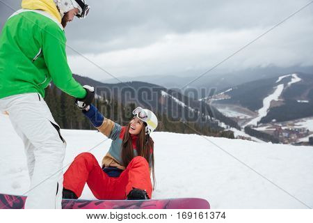 Picture of loving couple snowboarders on the slopes frosty winter day. Look at each other. Focus on woman.