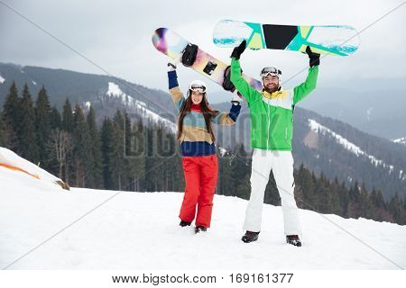 Picture of playful loving couple snowboarders on the slopes frosty winter day. Look at camera.