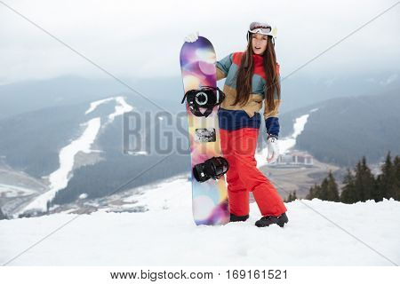 Photo of young lady snowboarder on the slopes frosty winter day holding snowboard in hands. Look at camera.