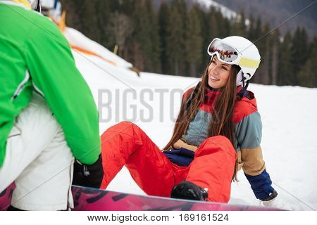 Image of cheerful loving couple snowboarders on the slopes frosty winter day. Look at each other. Focus on woman.