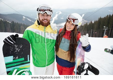 Image of happy loving couple snowboarders on the slopes frosty winter day. Look at camera.