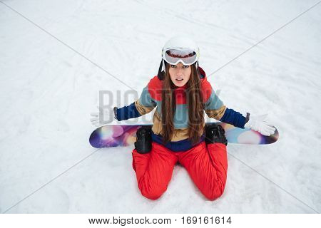 Picture of young confused lady snowboarder lies on the slopes frosty winter day. Look at camera.
