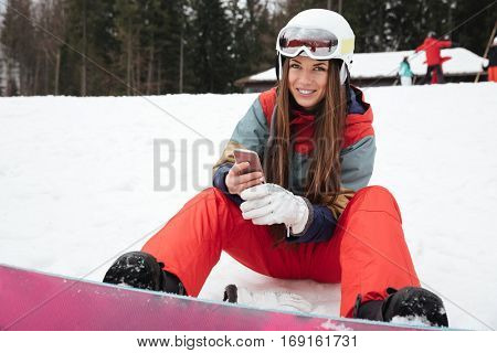 Photo of young happy lady snowboarder lies on the slopes frosty winter day while chatting by phone. Look at camera.