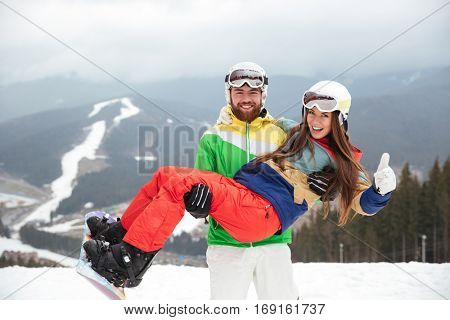 Photo of happy loving couple snowboarders on the slopes frosty winter day. Look at camera. Man holding lady on hands.