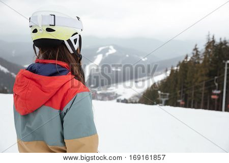 Back view image of young lady snowboarder on the slopes frosty winter day.