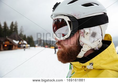 Portrait of handsome man snowboarder on the slopes frosty winter day. Looking aside.