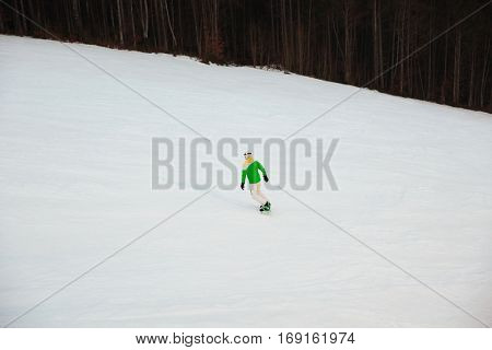 Back view picture of young man snowboarder on the slopes frosty winter day.