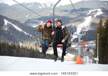 Picture of young happy loving couple sitting in ropeway over mountains. Looking at camera and waving.