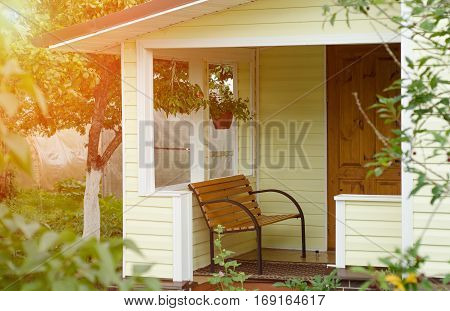 Entrance porch decorated with antique bench, big flower pots with flowers. Russian Federation