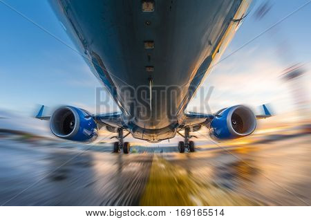 Airplane in motion during takeoff and landing, on a background of sunset and wet runway