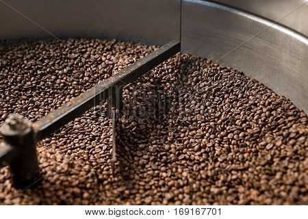 Freshly roasted coffee beans get sifted and stirred in  roasting machine