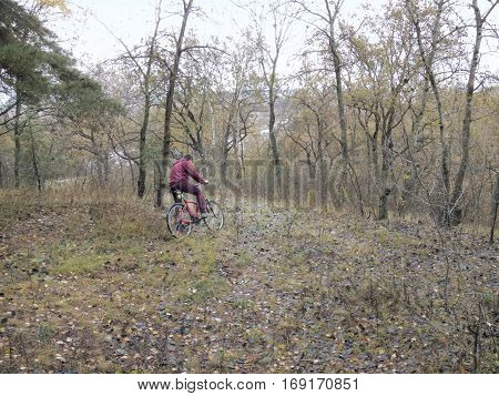 guy on the red bicycle stopped in the uncharted rugged terrain