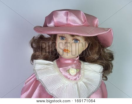 Porcelain doll with a delicate baby face expressive features clothing in retro style