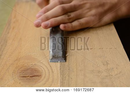 Carpentry working with chisels a wooden board - close-up