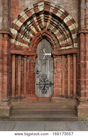 Arched medieval Gothic stone doorway with hinges, patterns, St. Magnus Cathedral, Kirkwall, Orkney, Scotland