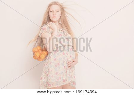 Pregnant woman holding fruits.  Nutrition and diet during pregnancy. Beautiful pregnant woman standing with oranges