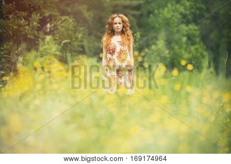Beautiful woman outdoors enjoying nature in dress at summer meadow.
