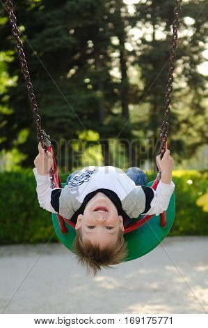 Kid toddler boy swinging on a playground. Joyful boy on swing in a park.