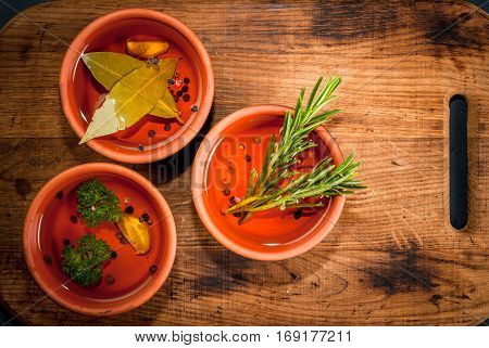 Selection of scented oils from herbs and spices: rosemary garlic pepper parsley bay leaf. On a cutting board on a dark gray stone kitchen table. Top view copy space
