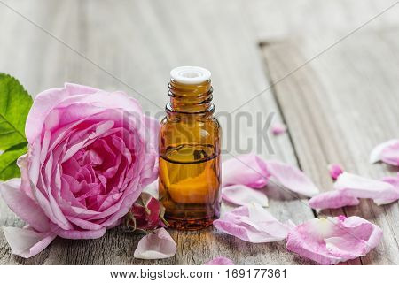 Dark glass vial with rose essential oil and flower of pink rose on a wooden background