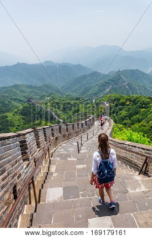 Woman backpacker student walking down the stairs overlooking the landscape of the Great Wall of China at famous Badaling tourist destination during travel vacation in Beijing. Asia summer holidays.