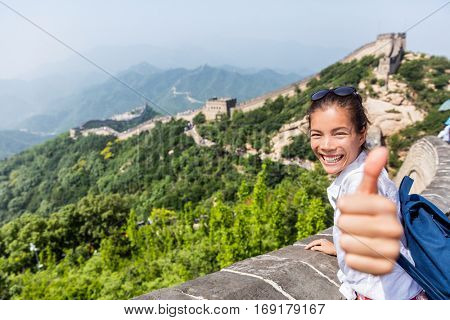 Happy tourist girl at Great Wall of China doing thumbs up hand sign having fun at famous Badaling ruins during travel holidays at Chinese destination. Asia vacation.