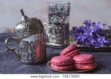 pink French macarons and Turkish coffee in a traditional cup