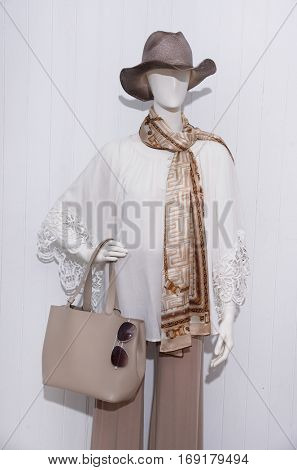 female clothing with hat and scarf, bag, sunglasses on mannequin
