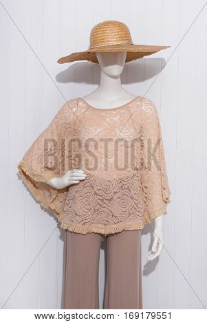 female clothing with hat on mannequin-wooden background