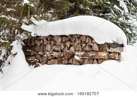 Supply of wood for the winter. Firewood. Snow covered firewood.