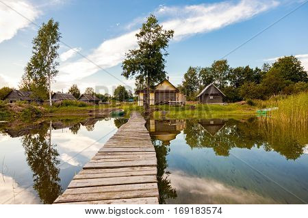 Traditional russian wooden baths at the bank of lake in summer day