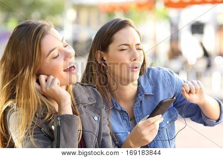 Joyful friends listening to music on line from a smart phone and singing sharing earphones in the street
