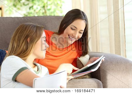 Students studying and helping each other with notebooks on a sofa in the living room at home