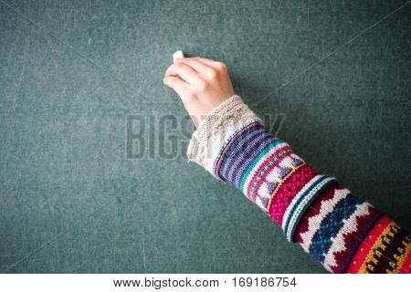 Hand in a winter Christmas pullover in patterns writing message on a chalkboard at school