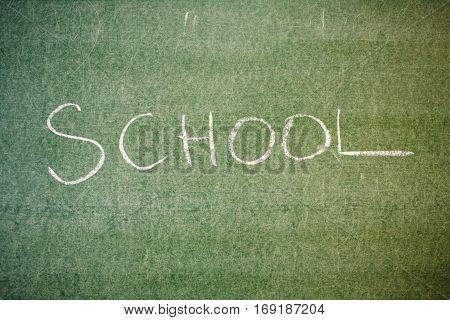 Handwritten message on a chalkboard at school: school