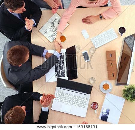 Business people sitting and discussing at meeting, in office.