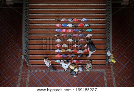 Seville, Spain - 19 August 2016. A group of men are selling typical Spanish fans in a stairway in Plaza de Spana in Seville, Spain.