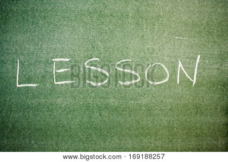Handwritten message on a chalkboard: lesson. at school