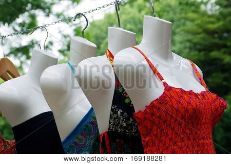 Feminine swim suits on mannequins hanging for sale in a shop