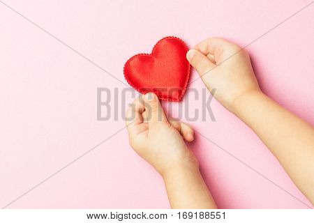 Children's hands holding the heart on a pink background. Concept of love care faith hope purity. Place for text. Flat fly
