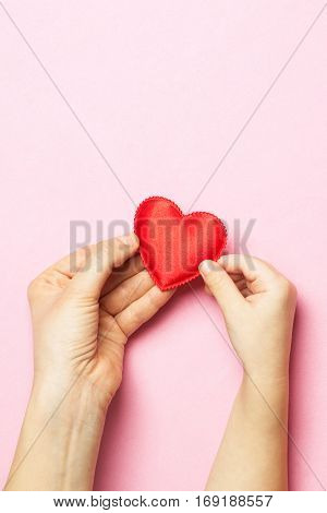 Women's hands holding the child's hand with a heart. The concept of motherhood caring family protection love. Place for text. Flat fly