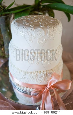 White wedding cake with colorful ribbon tied around it. Selective focus