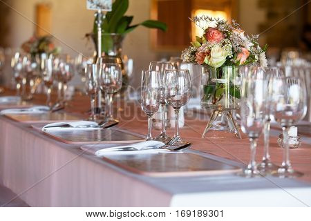 Table covered with tablecloth at wedding reception decorated with flowers in vases. Selective focus on glasses