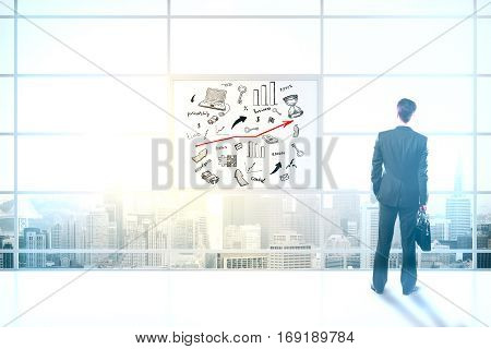 Back view of businessman holding briefcase and looking out of window in interior with city view and business drawing. Success concept. 3D Rendering