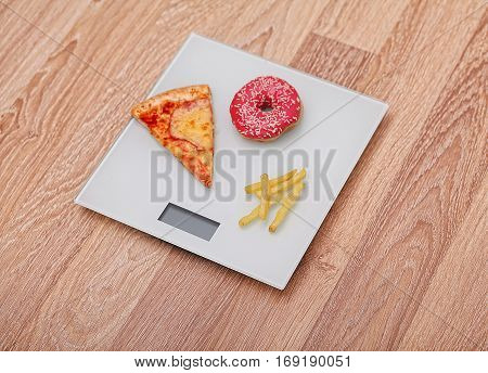Diet. The concept of junk food on weight. Healthy Lifestyle. Wooden background.