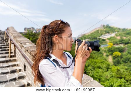 Young asian woman photographer taking pictures with professional photo gear on China famous attraction the Great Wall. Female photography hobby lover focused taking photos with slr camera.